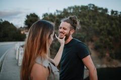 Couples ayant l'amusement en nature Femme tenant le visage d'homme avec le Han Photographie stock