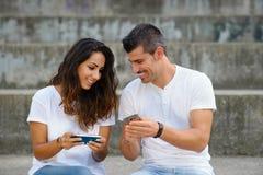 Couples ayant l'amusement et le jeu avec des smartphones Photo stock