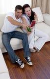 Couples ayant l'amusement jouer des jeux vidéo Photo stock