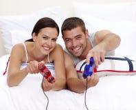 Couples ayant l'amusement jouer des jeux vidéo dans le bâti Images stock