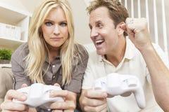 Couples ayant l'amusement jouer le jeu visuel de console Photo stock