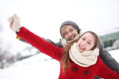 Couples ayant l'amusement le jour de l'hiver Image libre de droits