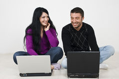 Couples ayant l'amusement sur des ordinateurs portatifs Image stock