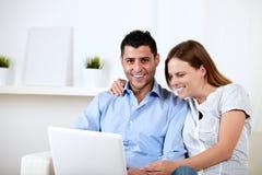 Couples ayant l'amusement sur l'ordinateur portatif à la maison Photos libres de droits