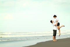 Couples ayant l'amusement sur la plage Photographie stock libre de droits