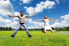 Couples ayant l'amusement sur le pré Photo libre de droits
