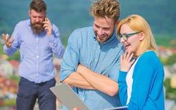 Couples ayant l'amusement tandis que surfing sur Internet extérieur Appel mobile de vidéoconférence d'utilisation de collègues à  photo libre de droits