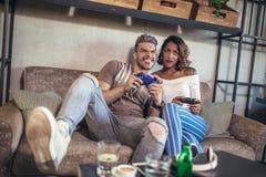 Couples ayant l'amusement tout en jouant des jeux vidéo Photographie stock
