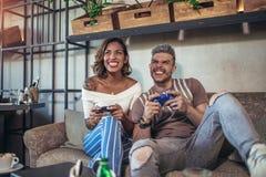 Couples ayant l'amusement tout en jouant des jeux vidéo Images libres de droits