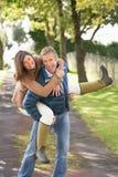 Couples ayant l'amusement tout en marchant dans le stationnement Photos stock