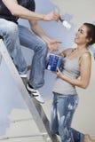 Couples ayant l'amusement tout en peignant la Chambre d'Unrenovated image libre de droits