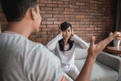 Couples ayant l'argument sur le divan photos stock