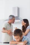 Couples ayant le conflit devant leur fils triste images stock