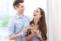 Couples ayant le pain grillé dans la nouvelle maison Photo libre de droits
