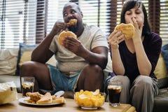 Couples ayant les aliments de préparation rapide sur le divan Images stock