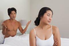 Couples ayant un argument dans le lit images stock