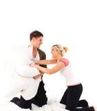 Couples ayant un combat d'oreiller dans le bâti Photographie stock