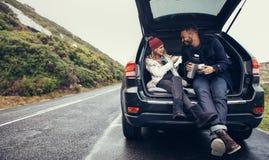 Couples ayant une pause-café pendant le voyage par la route Image libre de droits