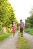 Couples bavarois heureux dans le soleil de soirée Images stock