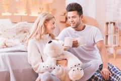 Couples beaux positifs tenant des tasses de thé image stock