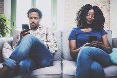Couples bouleversés d'afro-américain détendant ensemble sur le sofa Jeune homme de couleur et son amie à l'aide des smartphones t Photo libre de droits