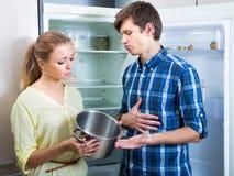 Couples bouleversés de famille regardant les étagères vides Image stock