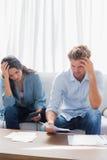 Couples bouleversés faisant leurs comptes Images stock