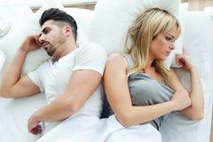 Couples bouleversés se trouvant de nouveau au dos dans le lit Photos libres de droits