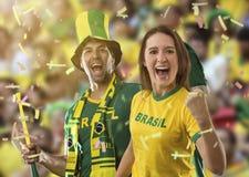 Couples brésiliens célébrant sur un stade photo stock