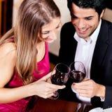 Couples buvant les glaces tintantes de vin rouge Photographie stock libre de droits