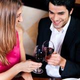 Couples buvant les glaces tintantes de vin rouge photo stock
