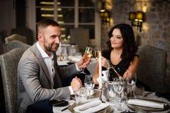 Couples célébrant dans le restaurant Photographie stock libre de droits