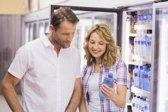 Couples cacual de sourire regardant la bouteille d'eau Photo libre de droits