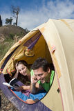 Couples campant la tente, le relevé et en parlant Photos stock