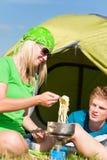 Couples campants de jeunes faisant cuire le repas en dehors de la tente Photographie stock libre de droits