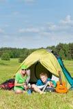 Couples campants de jeunes faisant cuire le repas en dehors de la tente Photos libres de droits