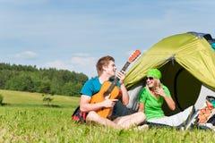 Couples campants jouant la guitare par la campagne de tente Photo stock