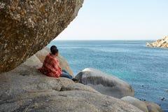Couples caressés se reposant sur les roches, donnant sur l'océan Images libres de droits