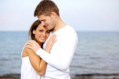Couples caressant à la plage semblant heureuse Photo stock