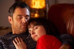 Couples caressant sur le sofa par le feu de bois confortable Photographie stock