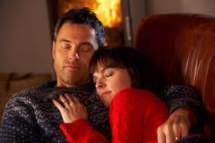 Couples caressant sur le sofa par le feu de bois confortable Image libre de droits