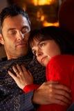 Couples caressant sur le sofa par le feu de bois confortable Photos libres de droits
