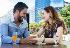 Couples caucasiens d'amour jugeant des mains dans un restaurant extérieures pendant l'été Photos stock