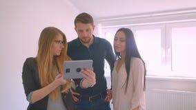 Couples caucasiens d'apparence d'agent immobilier jeunes l'appartement à vendre démontrant les occasions sur le comprimé clips vidéos