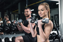 Couples caucasiens des athlètes s'exerçant avec des haltères au gymnase ensemble Photographie stock libre de droits