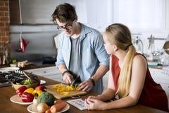 Couples caucasiens faisant cuire dans la cuisine ensemble Photographie stock libre de droits
