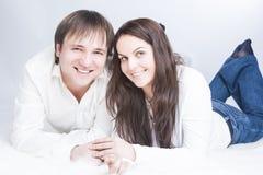 Couples caucasiens heureux et positifs ayant le temps communiquant ensemble sur le plancher les uns avec les autres Photos stock