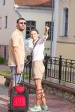 Couples caucasiens heureux et positifs voyageant avec la valise de chariot Image libre de droits