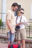 Couples caucasiens heureux et positifs voyageant avec la valise de chariot Image stock
