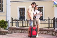 Couples caucasiens heureux et positifs voyageant avec le chariot Photographie stock